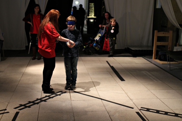 A picture of a teenager taking part in a blindfolded experiment at the Science Museum.