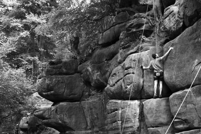 A black and white image of a man climbing Harrisons Rocks in Tunbridge Wells