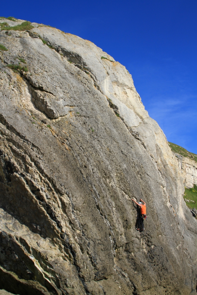 A rock climber starting a huge boulder climb.