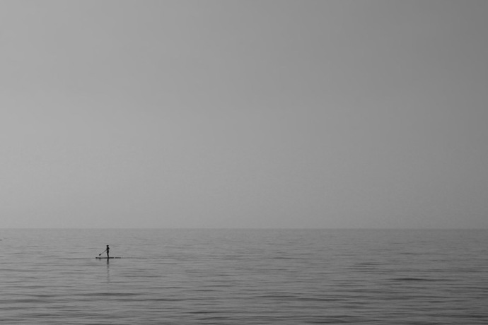 A Stand Up Paddler on a becalmed ocean.
