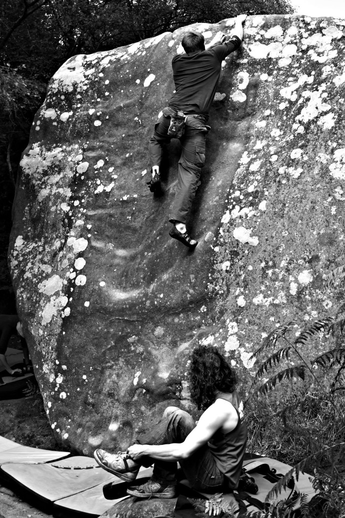 An image of a man about to slide down a boulder in Brimham.